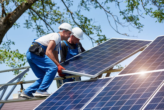 Two young technicians installing heavy solar photo voltaic panel on tall steel platform on green tree background. Exterior solar panel voltaic system installation, dangerous job concept.