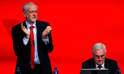 The Labour Party's shadow Chancellor of the Exchequer John McDonnell is applauded by party leader Jeremy Corbyn at the party's conference in Liverpool