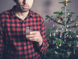 Sad and depressed man with drink at christmas