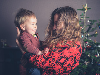 Young mother and happy toddler by christmas tree