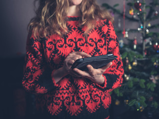 Woman using tablet by christmas tree