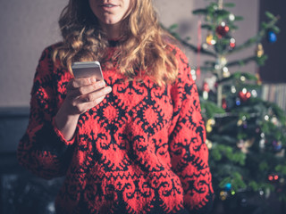 Young woman using smartphone by christmas tree