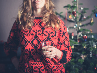 Woman with drink by christmas tree