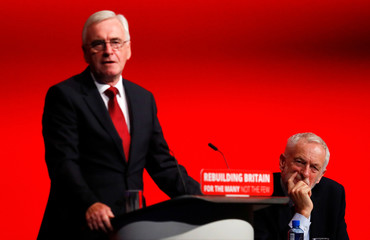 The Labour Party's shadow Chancellor of the Exchequer John McDonnell speaks as party leader Jeremy Corbyn looks on at the party's conference in Liverpool
