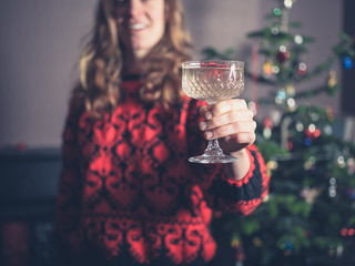 Happy young woman with drink by christmas tree