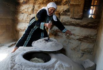 Palestinian woman bakes bread on a traditional oven near Ramallah, in the occupied West Bank