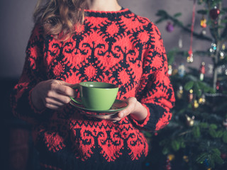 Young woman drinking tea by christmas tree
