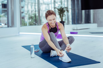 Sportswear. Positive mature woman tying shoelaces and seating on mat board