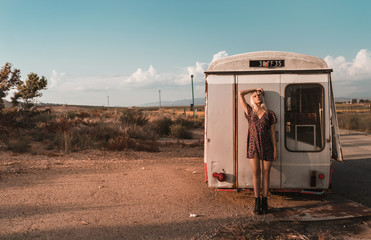 Distant view with copy space of young blonde woman resting on an old van in a sunset of summer blue sky and clouds background