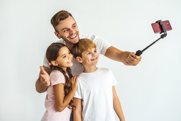 The father and kids taking a selfie on the white background