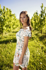 Pretty brunette girl is standing in a green dream-like orchard dressed in flower summer dress.