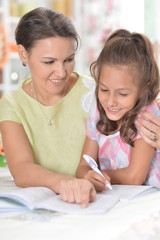 Cute little girl with her mother doing homework together