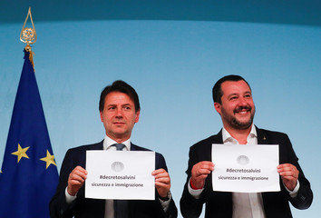 Italy's Prime Minister Conte and Interior Minister Salvini hold up pieces of paper with the name of the new decree written on them during a news conference at Chigi Palace in Rome