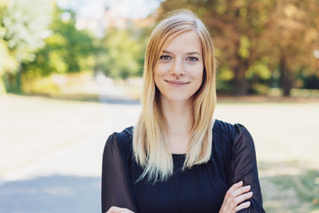 smiling young blond woman standing in city park
