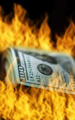 US Dollar bills in flames on black