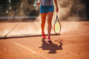 Female tennis player cleaning the court with drag mat.