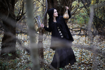 A woman in a witch suit in a forest