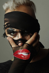 Closeup studio portrait of man, where the face of model is partially covered with stockings. Paper red lips on face