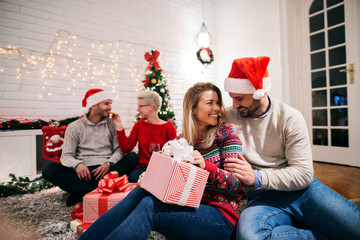 Young couples celebrating winter holidays together. One couple sitting on side and sharing presents.