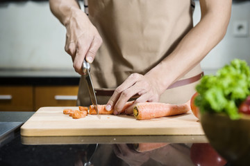 Close up view of man hand slicing carrot on the cutting board