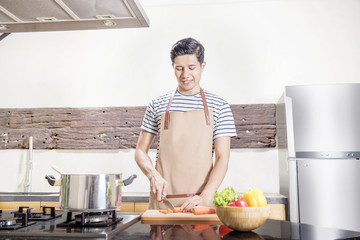 Handsome asian man slice the carrot for cooking