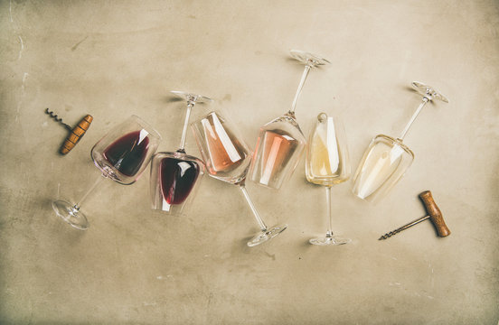 Flat-lay of red, rose and white wine in glasses and corkscrews over grey concrete background, top view, horizontal composition. Wine bar, winery, wine degustation concept