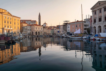 Venetian Port and The Main Square Tartini of Piran City at the sunriste reflected on Water in Slovenia.