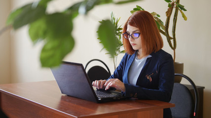 Young red hair officeworker women in glasses is printing on the laptop keyboard. Mid shot with leaves on background