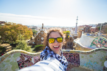 Young happy woman making selfie portrait with smartphone in Park Guell, Barcelona, Spain