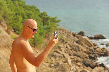 A young bald man takes a picture on a smartphone. In nature, against the background of mountains and the sea