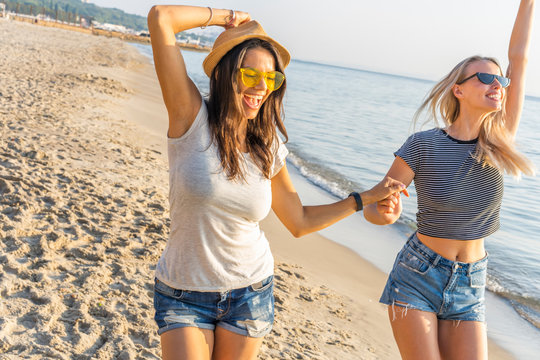 Happy young women strolling along coastline on a sunny day. Two female friends walking together on a beach, enjoying summer vacation.