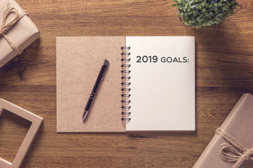 2019 goals list in notebook with gift box new year on wooden table background. Fototapete