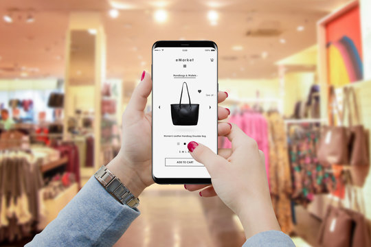 Girl in boutique searching for handbag on her smartphone to buy online