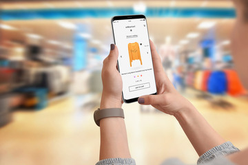 Woman in clothing store buying online yellow hoodie using her smartphone