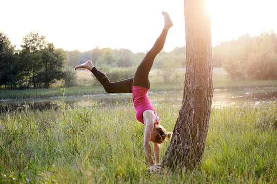 Sporty beautiful young woman doing handstand on a tree as a yoga exercise outdoors at sunset