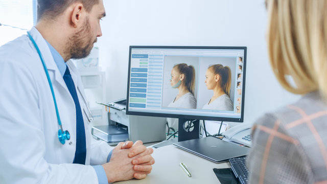 Plastic / Cosmetic Surgeon Consults Woman about Facial Lift Surgery, He Points at Computer Screen Showing Types of Facelift, Forehead Lift, Cheek Bones and Nose Correcting Procedures Available.