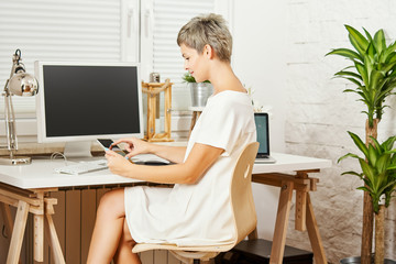 beautiful business woman in a white dress sitting at a desk and works on a tablet in a home office