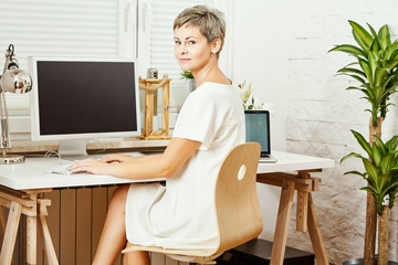 beautiful business woman in white dress sitting at desk and working on computer at home office
