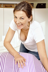 Cheerful woman makes bed with sheets in bedroom