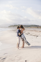 Young couple in love kissing on the deserted beach on a summer evening