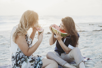 Young couple in love eat watermelon on the deserted beach on a summer evening