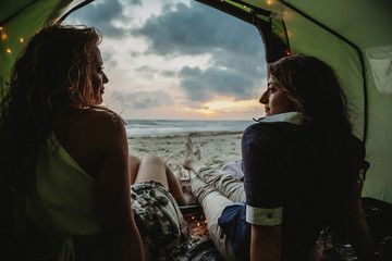 Young loving couple while camping on the seashore a summer evening at sunset. View from inside the tent