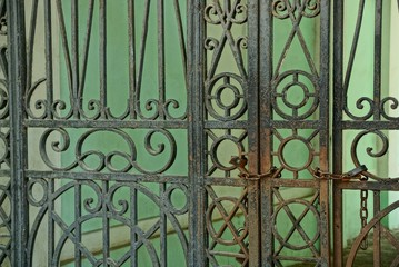 metal texture of black and rusty steel bars with a forged pattern on the gate