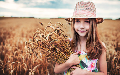 Girl with a hat in the wheat field