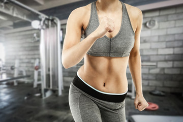 Slim young woman body in gym interior and free space for your decoration.