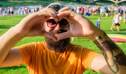 Man bearded hipster in front of crowd people show heart gesture riverside background. Cheerful fan love summer fest. Hipster happy celebrate event picnic fest festival. I love summer holiday festival