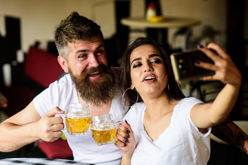 Couple in love on date drinks beer. Couple cheerful mood drinking beer in pub. Take selfie photo to remember great date in pub. Man bearded hipster and girl with beer glass full of craft beer
