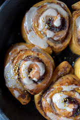 magical cinnamon rolls with white icing and gold stars in cast iron pan