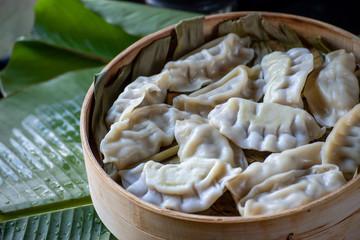 steamed pot stickers dumplings in bamboo basket on banana leaves