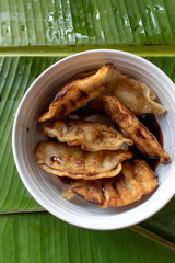 fried pot stickers dumplings with dipping sauce in bowl on banana leaves